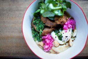 Grits cooked in cashew milk and topped with slow-roasted pork and pickled onions at El Rey Coffee Bar and Luncheonette on the Lower East Side.